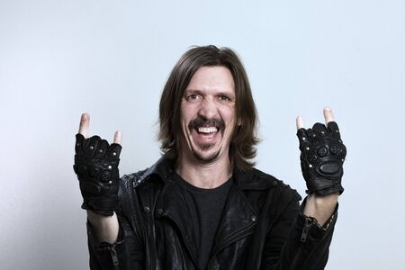 Smiling long-haired man in a black leather jacket and gloves makes a rock gesture on a white background. Conceptual rock fan or heavy metal music.