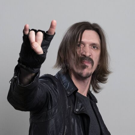 Long-haired man in a black leather jacket and gloves makes a rock gesture on a white background. The image of a rock fan. Heavy metal music concept. Square frame.