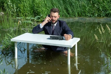 A harsh young boss in a suit swears on the phone. Office swamp concept. Funny situation of a businessman relaxing. Routine and daily work of a manager or technical support specialist.