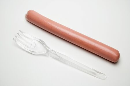 Sausage and a transparent fork on a white background. The concept of fast food, hunger or lack of food, cheap GMO products for one. Environmental issue and ban on plastic, poor student or senior citizen.