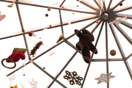 Part of the domed glass roof of a public space. Balls, a puppet man, a mittens and snowflakes hang on thin threads. New Year decorations in a supermarket, airport, shopping center. Christmas background. Copy space. Archivio Fotografico