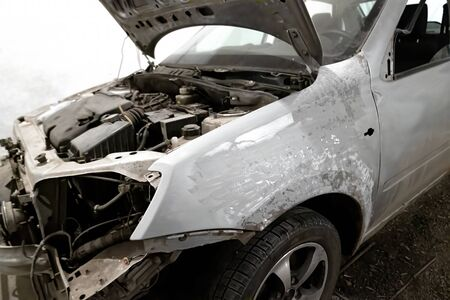 A car body element for painting after an accident with the help of grinding abrasive paper in a car repair shop. Vehicle repair in the garage. Recovery after a collision.