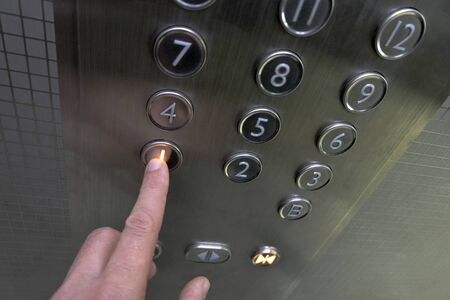 The hand presses on the first floor elevator button. A man in a metal elevator. A twelve-story building. Selective focus. Shallow depth of field. Blurry.