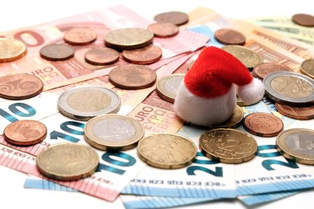 European money. The concept of New Year shopping and unexpected spending on the holidays. Finance and Santa Claus hat as a symbol of Christmas. Coins are on euro banknotes.