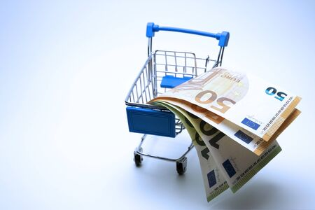 A souvenir trolley for a supermarket is filled with euro bills. European financial concept. Shopping with money. Online e-commerce. Copy space.