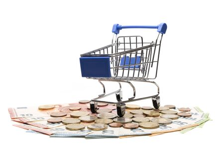 Shopping with money. A souvenir trolley for a supermarket stands on banknotes and euro coins. European financial concept. Online e-commerce. Copy space. Isolate.