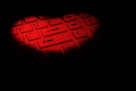 A computer keyboard is highlighted in red in the shape of a heart. Black background. Copy space. The concept of likes and love in the digital world of the Internet. Archivio Fotografico
