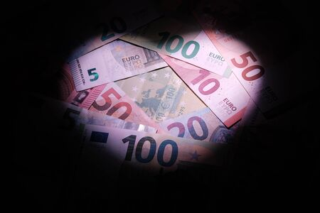 Euro money is backlit by a heart-shaped light. The concept of finance and love, banking. Copy space. Black background.