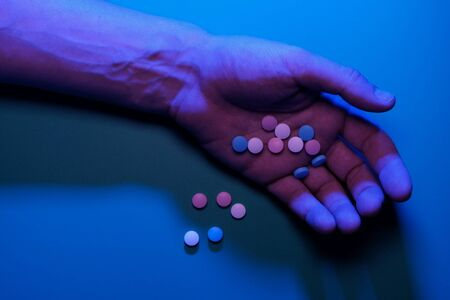 Danger of death. Man's hand with pills. Blue light. The concept of suicide, drug overdose, drug addiction, loss of consciousness. Copy space.