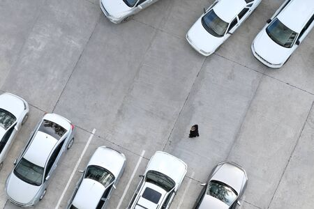 A man is walking in a car park. Driver, passerby or buyer of cars. Copy space. View from above.