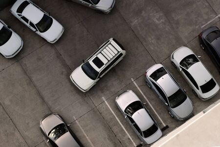 A car drives into an empty parking space among various other cars. View from above. Copy space. Concept.
