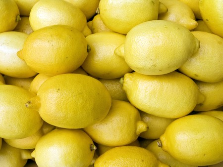 A pile of beautiful lemons on a counter photo
