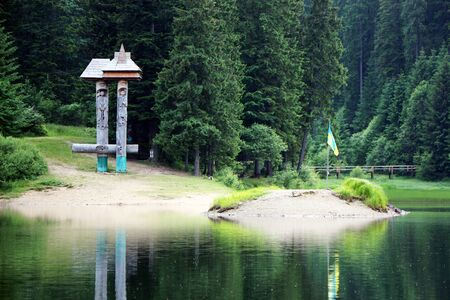 The sculpture and island on Lake Synevir in the Carpathian Mountain Stock Photo