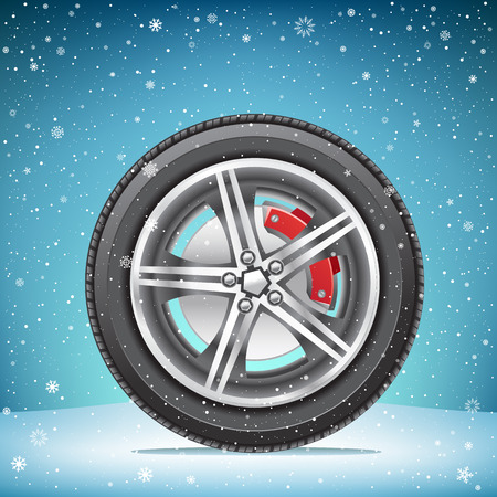 The winter inflated tire on blue snowy background. Wheel in the snow