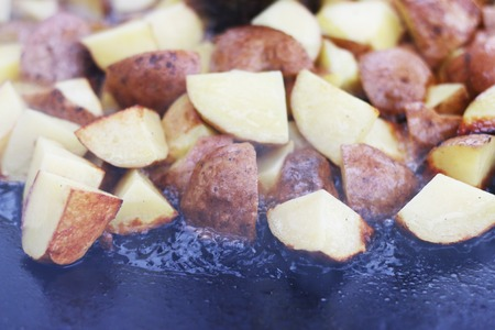 preperation: Frying raw potato in sunflower oil on large pan. Cooking potatoes
