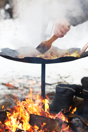 log fire: Frying raw potato in sunflower oil on big pan. Cooking potatoes. Burning big log fire in fireplace