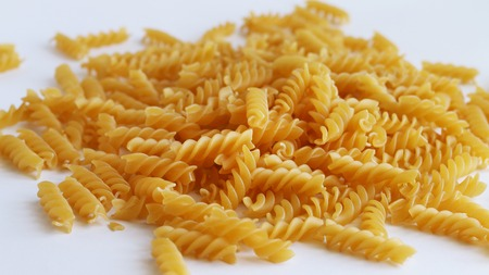 Spill spiral pasta on white background. Raw uncooked food macaroni Stock Photo