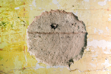 Hole in the old plaster wall. Destroyed round shape in building facade. Construction material background Stockfoto