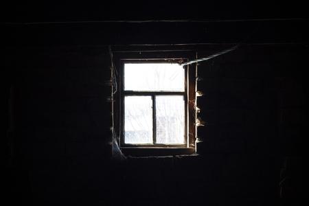 Vieille fenêtre en bois dans l'obscurité. La lumière du soleil à l'extérieur, l'obscurité à l'intérieur Banque d'images