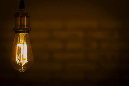 Led lamp shining warm light in dark wallbrick background. Light bulb shine in darkness Banque d'images