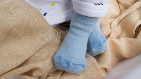 newborn baby feet in blue socks closeup
