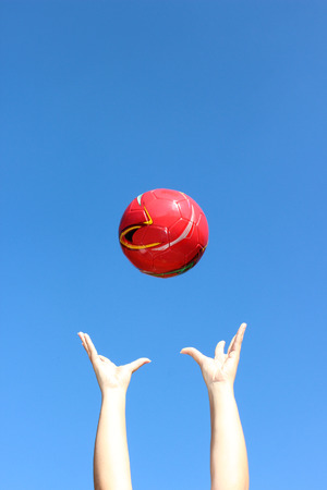 the thrown: Red ball thrown in the air and blue sky Stock Photo