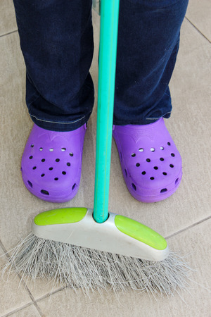 brooming: Person holding a broom and wearing crocs Stock Photo