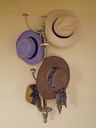 coat rack: Panama hats and straw hats hanging on a coat rack. Stock Photo