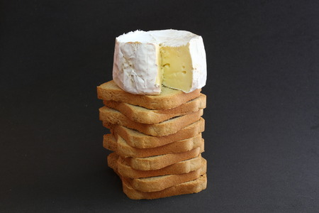 greediness: Cheese on a pile of toasts in a black background