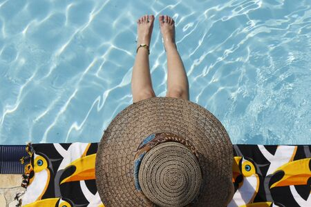 legitimate: Girl at the pool with a hat Stock Photo