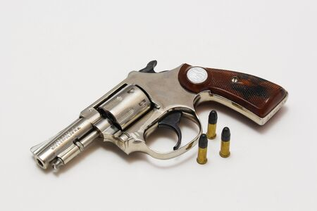 Revolver with bullets on white background.