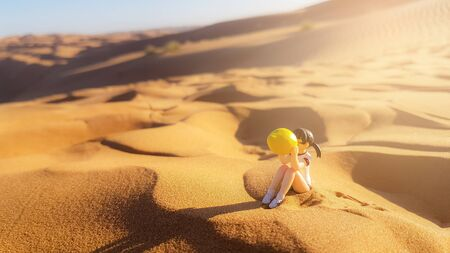 Little girl drinking lemonade dessert to relieve the heat.Natural landscape of sand sweltering. Stock Photo