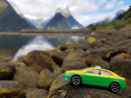 Model car on the stone behind a mountain view with snow cover.That seems to be driven on a hill.