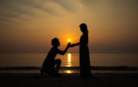 propose: A man propose marriage to a woman with sunrise background