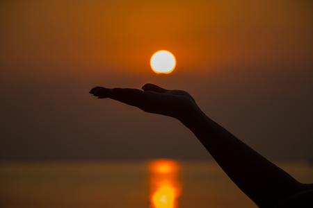 iluminado a contraluz: Una mujer con retroiluminación mano a elevar el sol