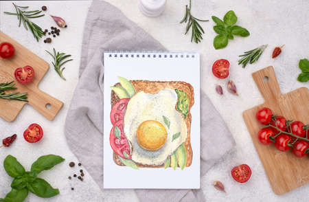 Watercolor illustration on page of notebook on the table on background of ingridienst for cooking meal. Fried egg toast with avocado, tomato and leaves of basilicum. Flatlay.