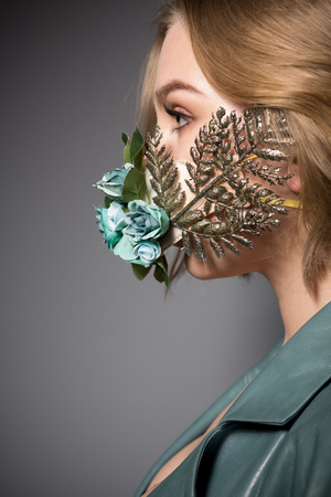 Profile of a beautiful girl with a flower mask
