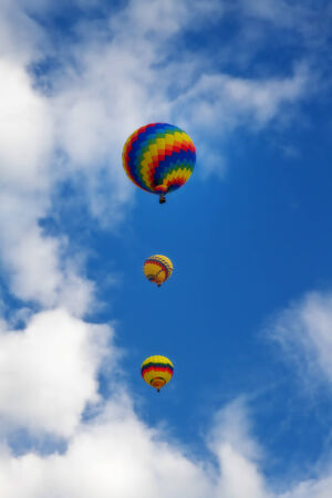 Three colorful hot air balloons ascending into the blue sky  The three balloons are vertical