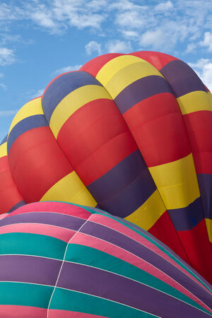 Close up of two Multi colored Hot air balloons against a blue cloudy sky