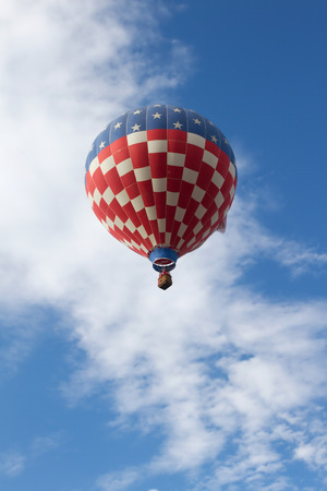 Red, White and Blue Hot Air Balloon flying in a blue cloudy sky