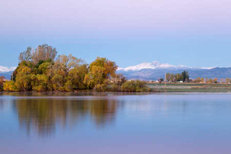 morning blue hour: fresh snow on Longs Peak as the fall leaves start to turn colorful on the Loveland Colorado lake
