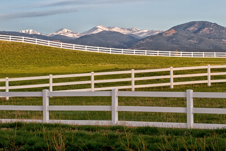 split rail: Springtime in Colorado. The sun lights up the green grass with the continental divide in the background.