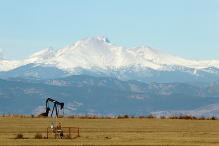 longs peak: A pumpjack pumping fuel with a snow-capped Longs Peak mountain in the background Stock Photo