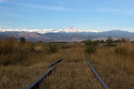 longs peak: Broken railroad tracks in a field leading to Longs Peak and the front range of Colorado Stock Photo