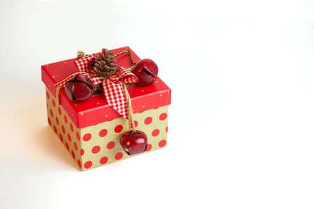 red polka dots: Una caja de regalo de Navidad decorado rústico en lunares rojos y un arco de algodón barato rematado con un cono de pino y cascabeles