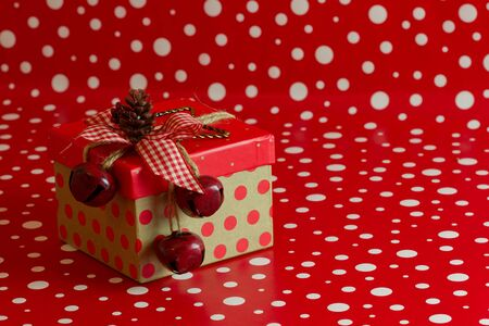 jingle bells: A country Christmas gift box with red polka dots and jingle bells topped with a pine cone on a red and white background