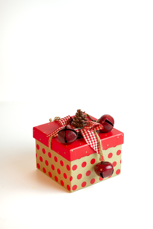 jingle bells: A country Christmas gift box with red polka dots and jingle bells topped with a pine cone