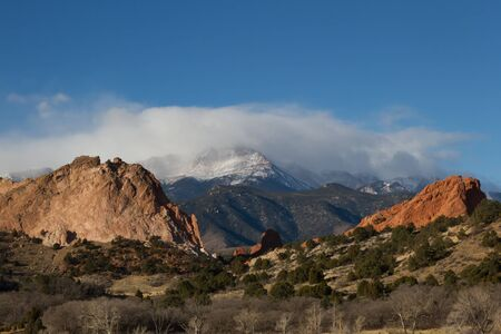 Clouds roll over the snow capped Pikes Peak with the Garden of the Gods in the foreground. This is located in the city of Colorado Springs