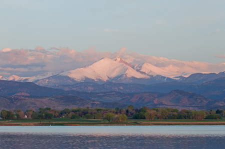 longs peak: Clouds roll over Colorados highest peak, Longs Peak, with McIntire Lake in the foreground Stock Photo