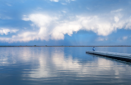 lon: A fisherman is fishing off the side of a dock as white cumulonimbus clouds are rolling in